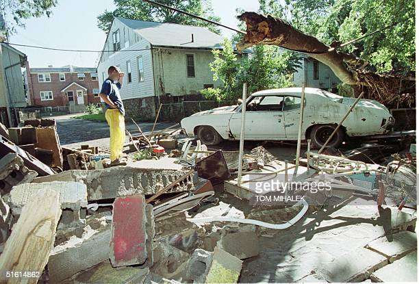 Joe Brown a resident of the 1400 block of Chestnut Street in Darby Boro PA looks at his neighbor's car 17 September 1999 and what little remains of a...