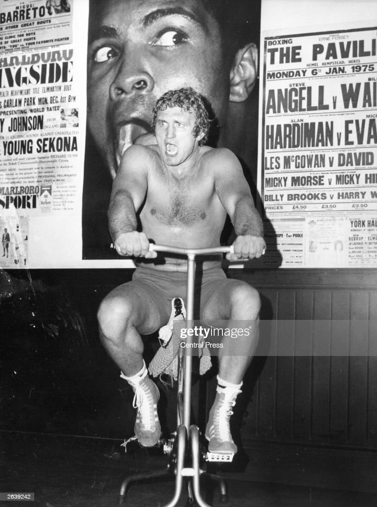 Joe Bugner training for his comeback fight against Richard Dunn at Wembley, London, when Dunn's British, Commonwealth and European titles will be at stake. Bugner impersonates the US boxer Muhammad Ali, on the poster behind him.
