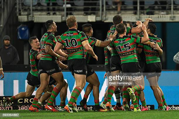 Joe Burgess of the Rabbitohs celebrates scoring a try with team mates during the round 24 NRL match between the South Sydney Rabbitohs and the...
