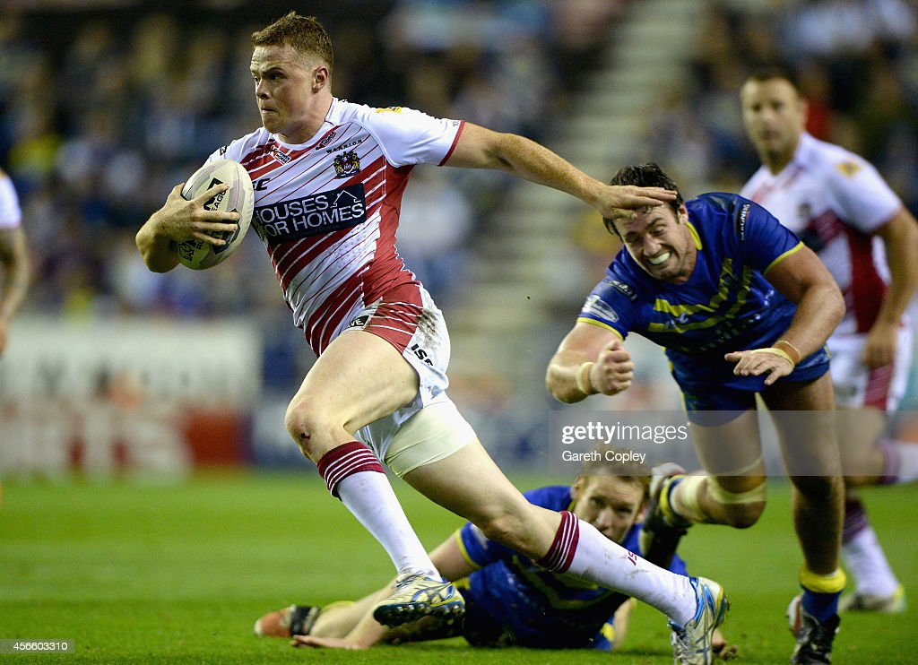 Joe Burgess of Wigan Warriors breaks the tackle of Stefan Ratchford and Joel Monaghan of Warrington Wolves during the First Utility Super League...