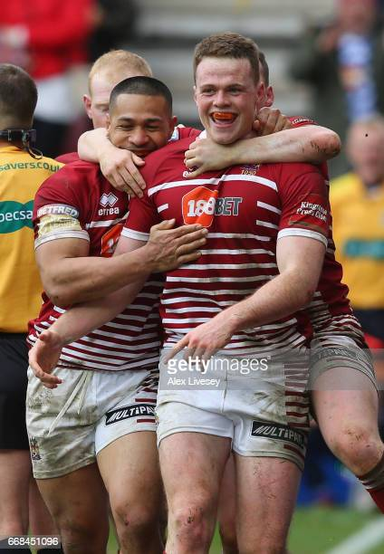 Joe Burgess of Wigan Warriors celebrates with team mates after scoring his second try during the Betfred Super League match between Wigan Warriors...