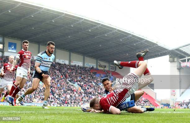 Joe Burgess of Wigan Warriors goes over for the opening try under pressure from Jesse Raimen of CronullaSutherland Sharks during the Dacia World Club...