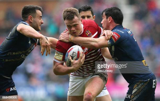 Joe Burgess of Wigan Warriors is tackled by Matty Smith of St Helens during the Betfred Super League match between Wigan Warriors and St Helens at DW...