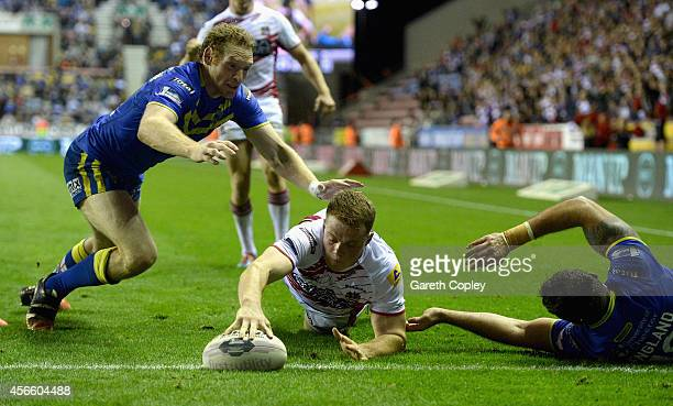 Joe Burgess of Wigan Warriors scores the winning try past Joel Monaghan of Warrington Wolves during the First Utility Super League Qualifying...