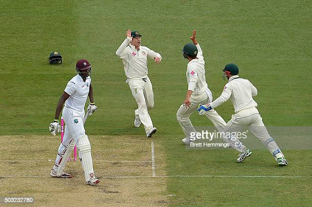 Joe Burns of Australia celebrates taking a catch to dismiss Jason Holder of West Indies during day one of the third Test match between Australia and...