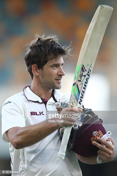 Joe Burns of the Bulls raises his bat after a century during day two of the Sheffield Shield match between Queensland Bulls and New South Wales Blues...