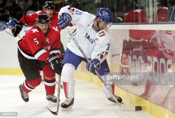 Joe Busillo of Italy controls the puck against the defense of Severin Blindenbacher of Switzerland during the men's ice hockey Preliminary Round...