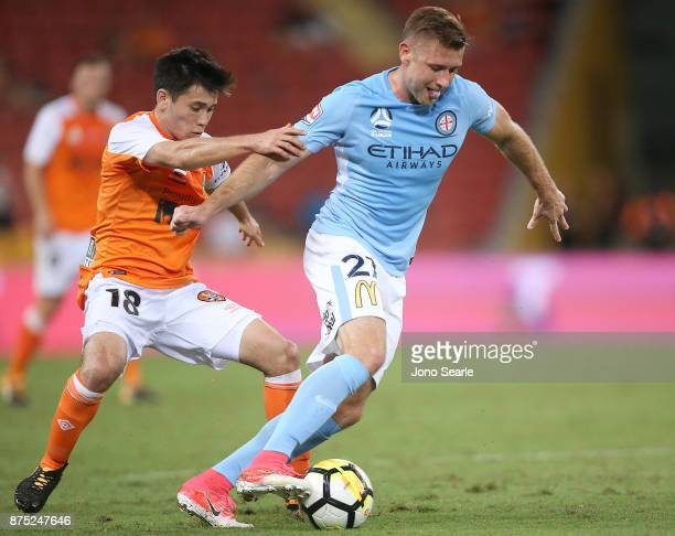 Joe Caletti of Brisbane and Marcin Budzinski of Melbourne contest the ball during the round seven ALeague match between Brisbane Roar and Melbourne...