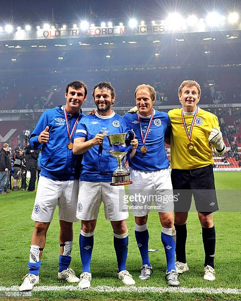 Joe Calzaghe Michael Sheen Woody Harrelson and Patrick Kielty pose with the trophy at Soccer Aid in aid of UNICEF at Old Trafford on June 6 2010 in...