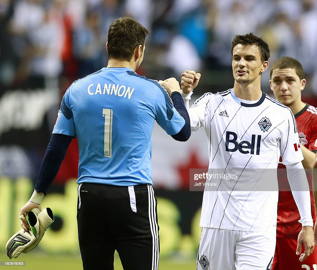 Joe Cannon #1 and Alain Rochet #4 of the Vancouver Whitecaps FC celebrate a victory while Hogan Ephraim #31 of the Toronto FC watches dejectedly during their MLS game March 2, 2013 at B.C. Place in Vancouver, British Columbia, Canada. Vancouver won 1-0.