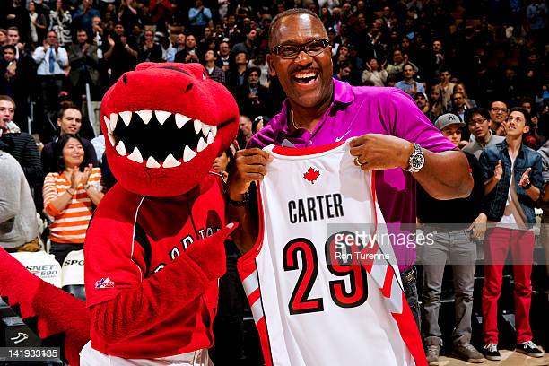 Joe Carter a former baseball player with the Toronto Blue Jays right poses with an honorary jersey given before a game between the Orlando Magic and...