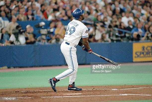 Joe Carter of the Toronto Blue Jays swings and watches the flight of his ball as he hit a game winning and World Series winning threerun home run in...