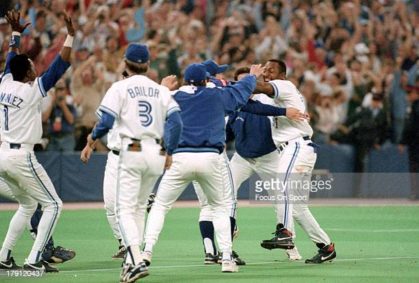 Joe Carter of the Toronto Blue Jays trotting around the base is met by teammates with jubilation after Carter hit a game winning and World Series...