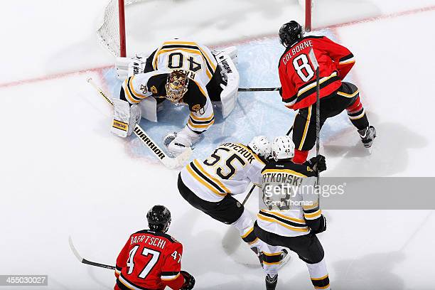 Joe Colborne and Sven Baertschi of the Calgary Flames take a shot at the goal against Tuukka Rask Johnny Boychuk and Matt Bartkowski of the Boston...