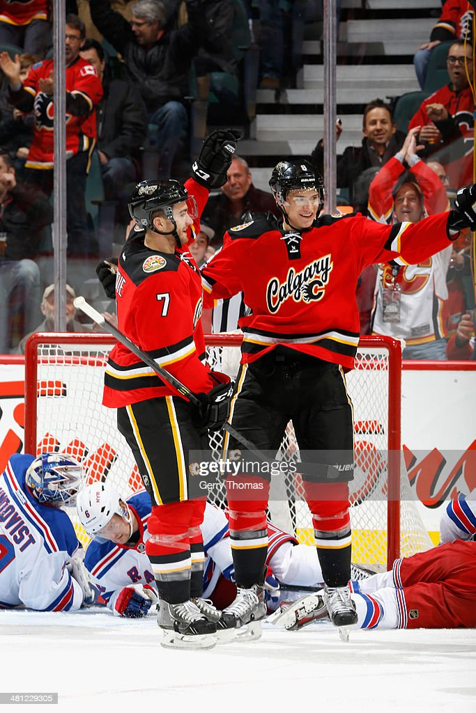 Joe Colborne #8 and T.J. Brodie #7 of the Calgary Flames celebrate a goal against the New York Rangers at Scotiabank Saddledome on March 28, 2014 in Calgary, Alberta, Canada.