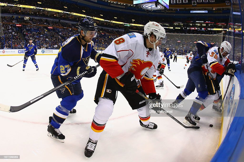 <a gi-track='captionPersonalityLinkClicked' href=/galleries/search?phrase=Joe+Colborne&family=editorial&specificpeople=5370968 ng-click='$event.stopPropagation()'>Joe Colborne</a> #8 and <a gi-track='captionPersonalityLinkClicked' href=/galleries/search?phrase=T.J.+Galiardi&family=editorial&specificpeople=4324979 ng-click='$event.stopPropagation()'>T.J. Galiardi</a> #39 both of the Calgary Flames fight for control of a loose puck against Alex Pietrangelo #27 and <a gi-track='captionPersonalityLinkClicked' href=/galleries/search?phrase=Jay+Bouwmeester&family=editorial&specificpeople=201875 ng-click='$event.stopPropagation()'>Jay Bouwmeester</a> #19 both of the St. Louis Blues at the Scottrade Center on November 7, 2013 in St. Louis, Missouri. The Blues beat the Flames 3-2.