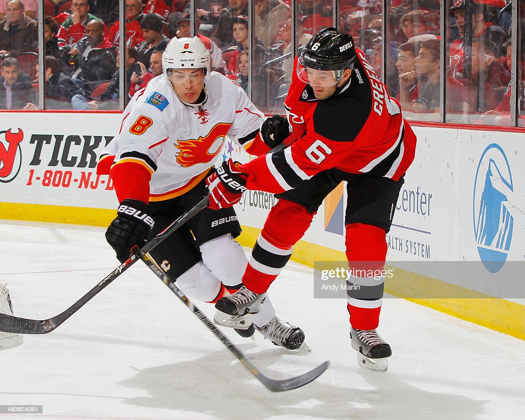 Joe Colborne #8 of the Calgary Flames and Andy Greene #6 of the New Jersey Devils battle for position during the game at the Prudential Center on April 7, 2014 in Newark, New Jersey.