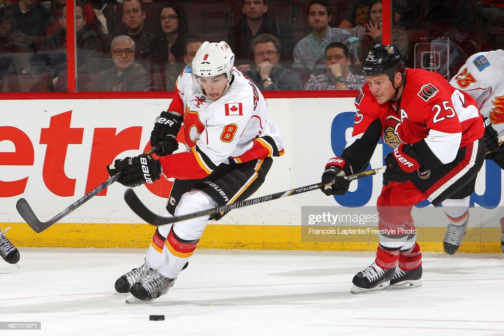 Joe Colborne #8 of the Calgary Flames controls the puck against Chris Neil #25 of the Ottawa Senators during an NHL game at Canadian Tire Centre on March 30, 2014 in Ottawa, Ontario, Canada.