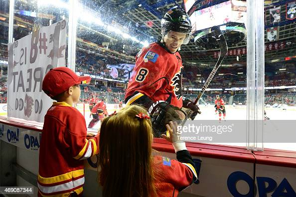 Joe Colborne of the Calgary Flames greets a young fan during the warmups against the Los Angeles Kings at Scotiabank Saddledome on April 9 2015 in...
