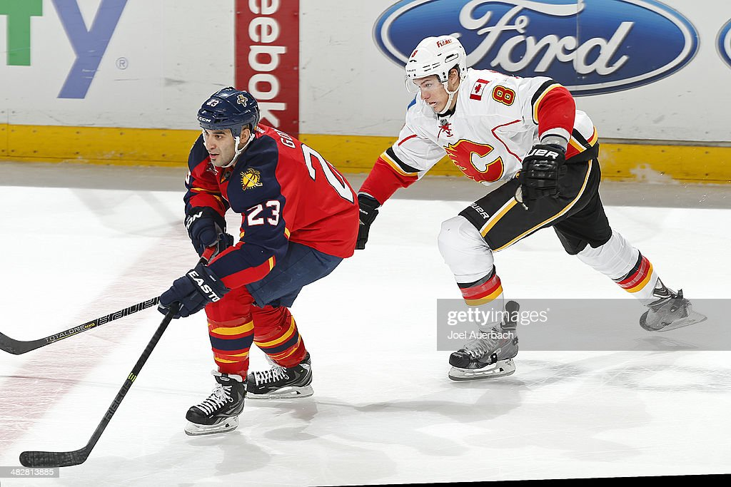 Joe Colborne #8 of the Calgary Flames pursues Scott Gomez #23 of the Florida Panthers as he skates up ice with the puck during the third period at the BB&T Center on April 4, 2014 in Sunrise, Florida. The Flames defeated the Panthers 2-1.