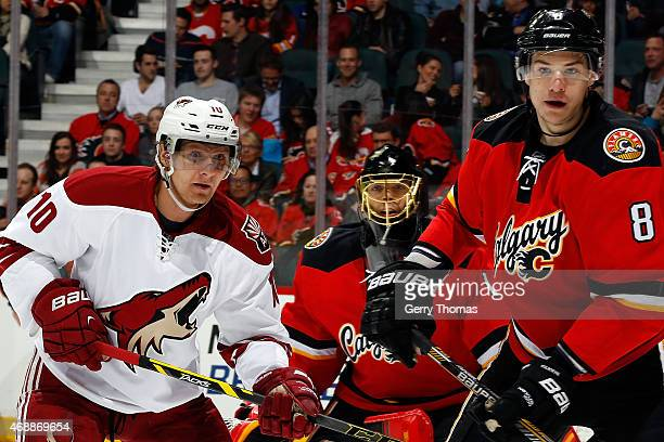 Joe Colborne of the Calgary Flames skates against Martin Erat of the Arizona Coyotes at Scotiabank Saddledome on April 7 2015 in Calgary Alberta...