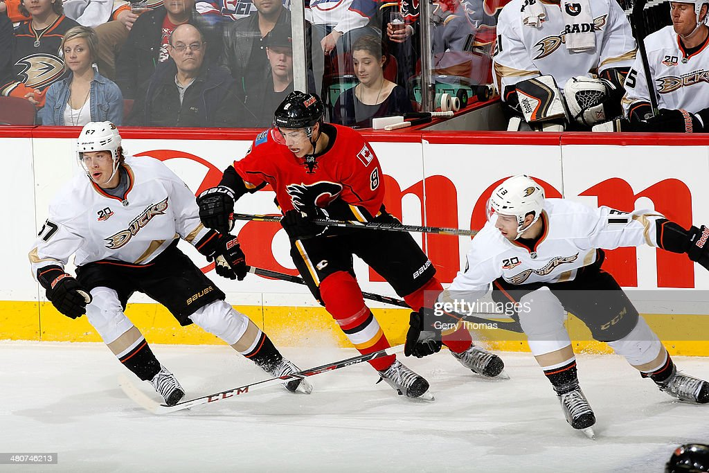 Joe Colborne #8 of the Calgary Flames skates against Nick Bonino #13 and Rickard Rakell #67 of the Anaheim Ducks at Scotiabank Saddledome on March 26, 2014 in Calgary, Alberta, Canada.