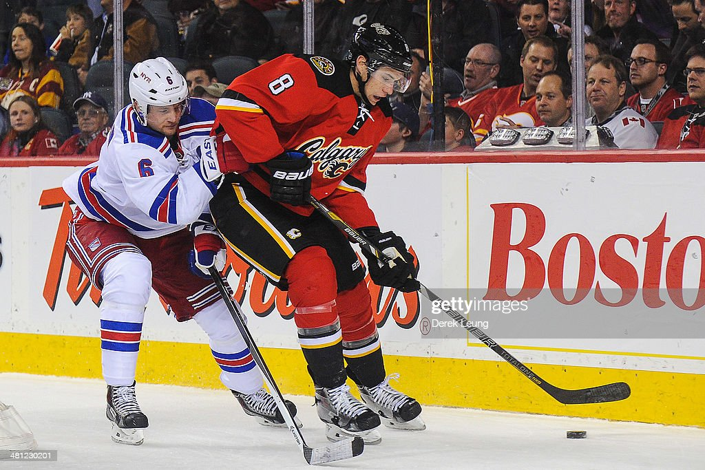 Joe Colborne #8 of the Calgary Flames skates with the puck past Anton Stralman #6 of the New York Rangers during an NHL game at Scotiabank Saddledome on March 28, 2014 in Calgary, Alberta, Canada. The Flames defeated the Rangers 4-3.