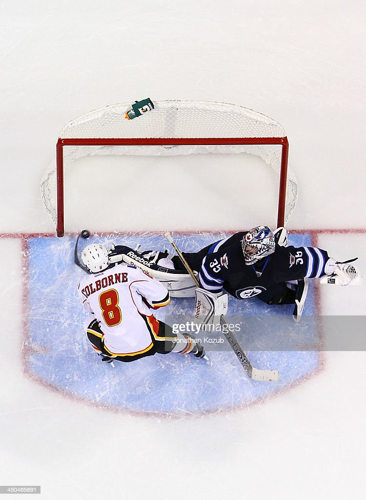 Joe Colborne #8 of the Calgary Flames slides the puck into the net after deking out goaltender Al Montoya #35 of the Winnipeg Jets during the shootout at the MTS Centre on November 18, 2013 in Winnipeg, Manitoba, Canada.