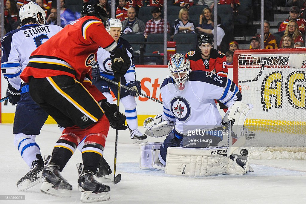 Joe Colborne #8 of the Calgary Flames takes a shot on Michael Hutchinson #34 of the Winnipeg Jets during an NHL game at Scotiabank Saddledome on April 11, 2014 in Calgary, Alberta, Canada.