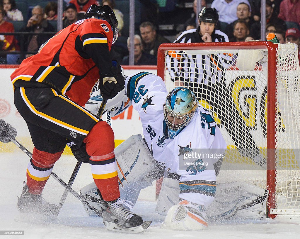 Joe Colborne #8 of the Calgary Flames takes a shot on the net of Alex Stalock #32 of the San Jose Sharks during an NHL game at Scotiabank Saddledome on March 24, 2014 in Calgary, Alberta, Canada.