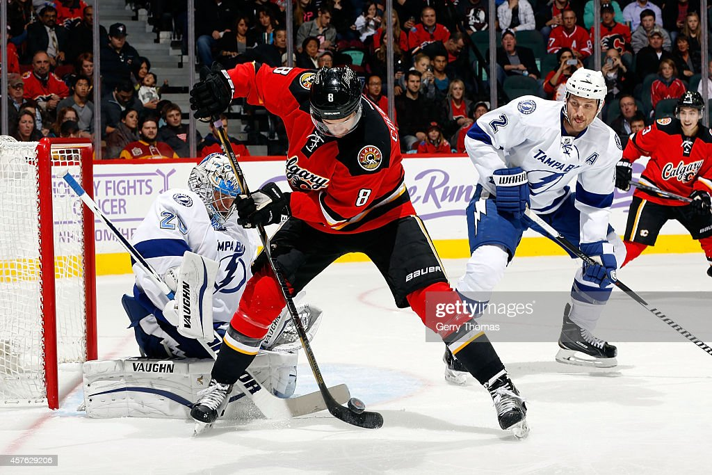 <a gi-track='captionPersonalityLinkClicked' href=/galleries/search?phrase=Joe+Colborne&family=editorial&specificpeople=5370968 ng-click='$event.stopPropagation()'>Joe Colborne</a> #8 of the Calgary Flames tries to re-direct a puck past goalie <a gi-track='captionPersonalityLinkClicked' href=/galleries/search?phrase=Evgeni+Nabokov&family=editorial&specificpeople=171380 ng-click='$event.stopPropagation()'>Evgeni Nabokov</a> #20 of the Tampa Bay Lightning at Scotiabank Saddledome on October 21, 2014 in Calgary, Alberta, Canada.