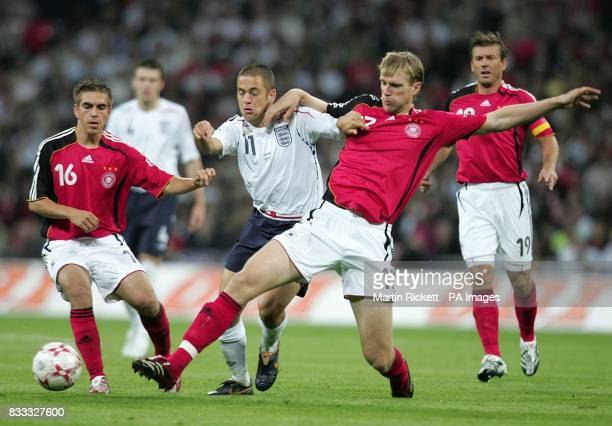 Joe Cole England battles for the ball with Germany's Per Mertesacker and Philip Lahm