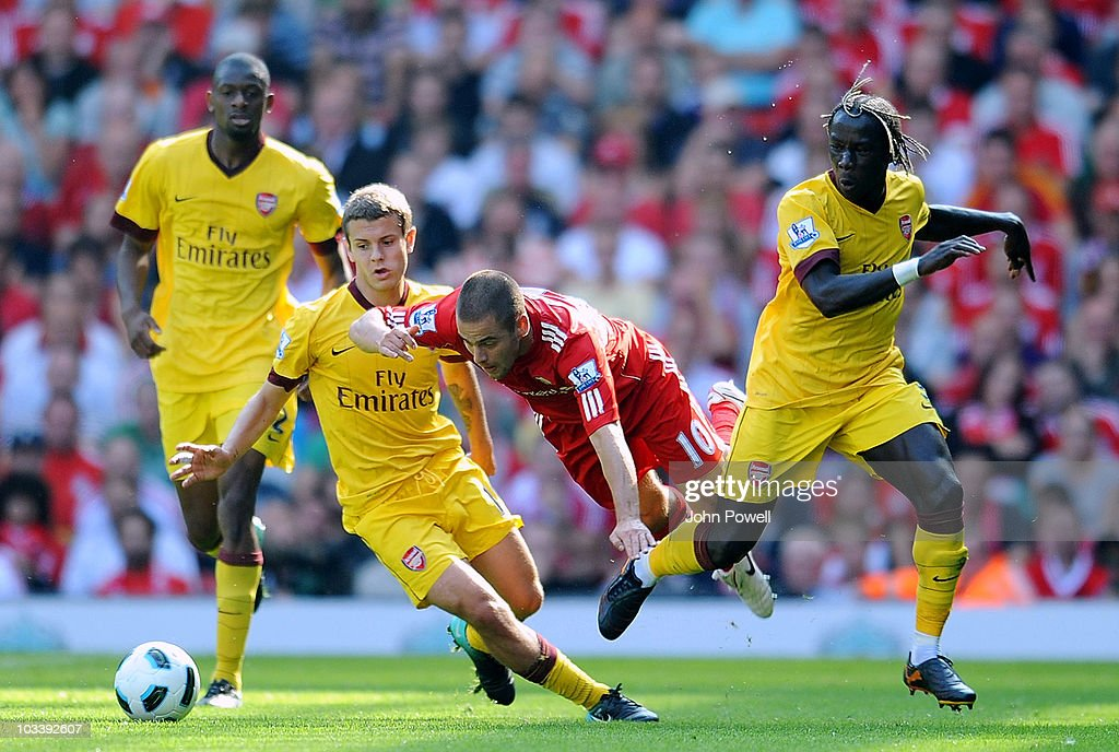 Joe Cole (2nd R) of Liverpool is sent flying by Jack Wilshere (2nd L) and Bacary Sagna (R) of Arsenal during the Barclays Premier League match between Liverpool and Arsenal at Anfield on August 15, 2010 in Liverpool, England.