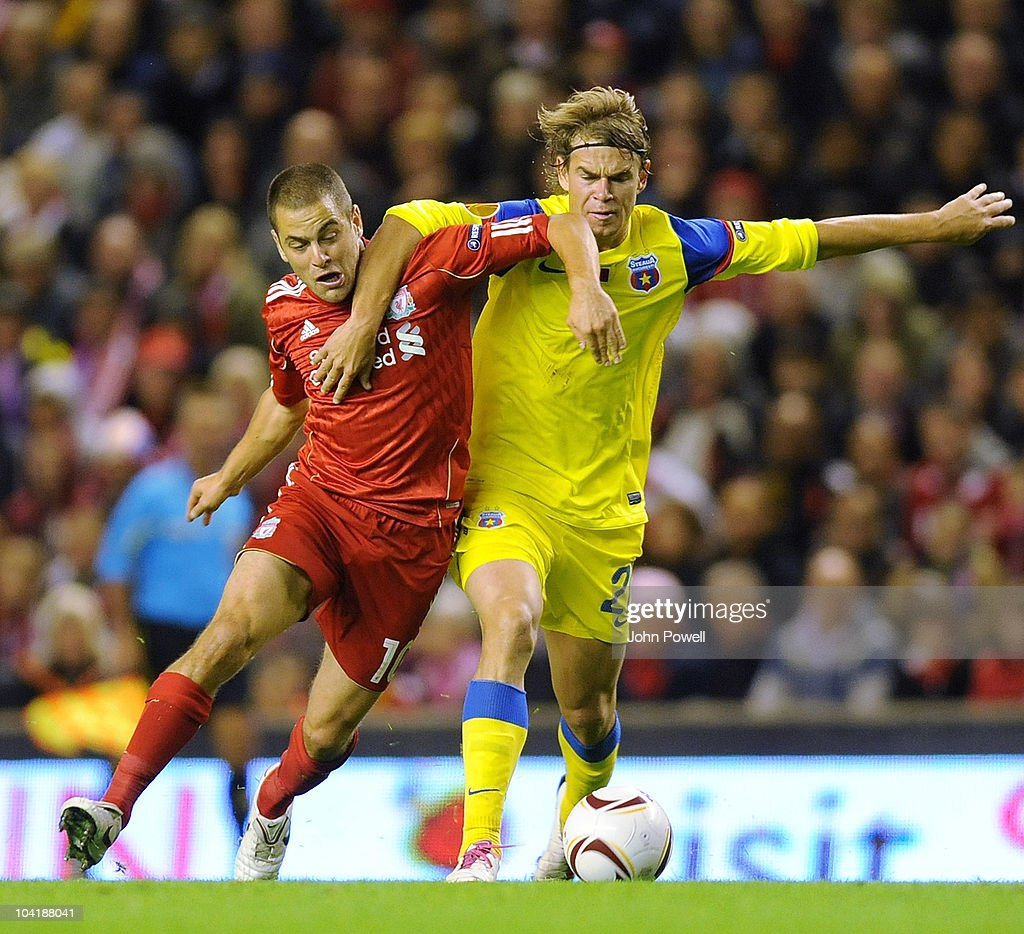 Joe Cole of Liverpool tussles with Eric Bicfalvi of Steau Bucharest during the first leg UEFA Europa League match between Liverpool and Steau Bucharest on September 16, 2010 in Liverpool, England.