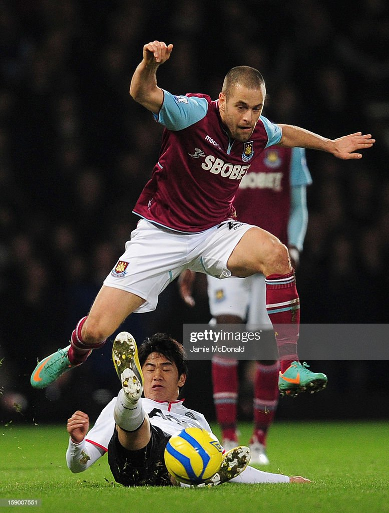 Joe Cole of West Ham United leaps over the tackle by Shinji Kagawa of Manchester United during the FA Cup with Budweiser Third Round match between West Ham United and Manchester United at the Boleyn Ground on January 5, 2013 in London, England.
