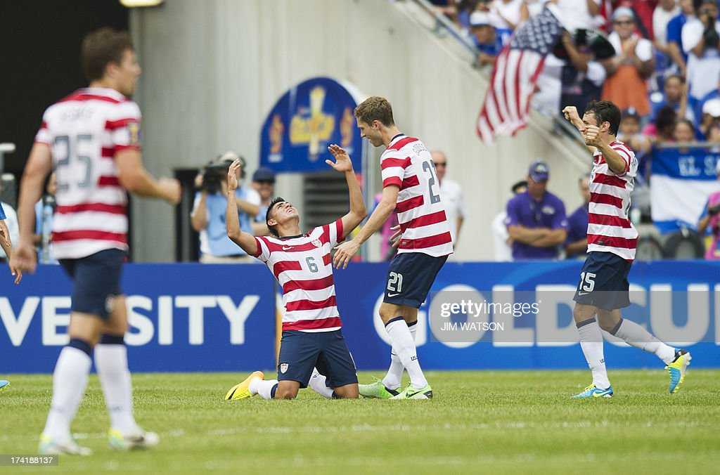 Joe Corona (C) drops to his knees after scoring a goal against El Salvador in the first half of a CONCACAF Gold Cup quarterfinal match in Baltimore on July 21, 2013.