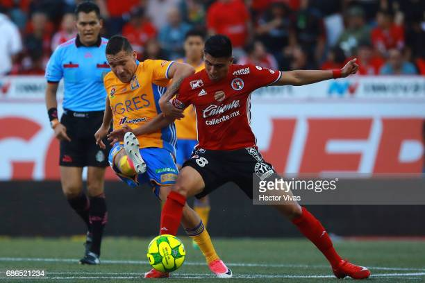 Joe Corona of Tijuana struggles for the ball with Jesus Dueñas of Tigres during the semi final second leg match between Tijuana and Tigres UANL as...