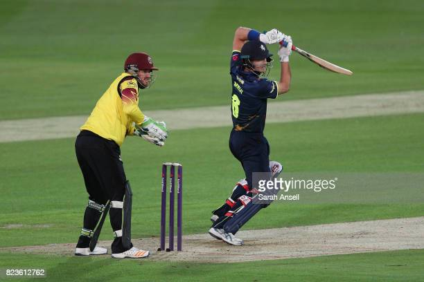 Joe Denly of Kent Spitfires hits a boundary as Somerset wicket keeper Steven Davies looks on during the NatWest T20 Blast South Group match at The...