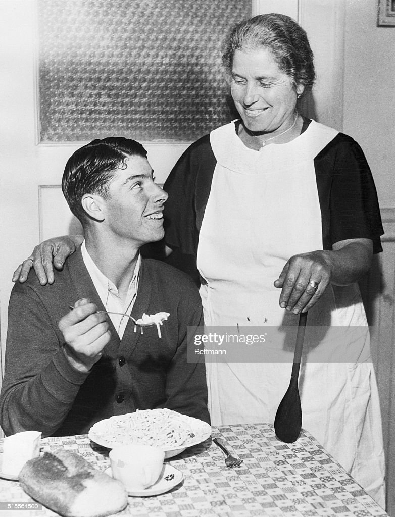 Joe DiMaggio eating spaghetti while his mother Rosalie looks on.