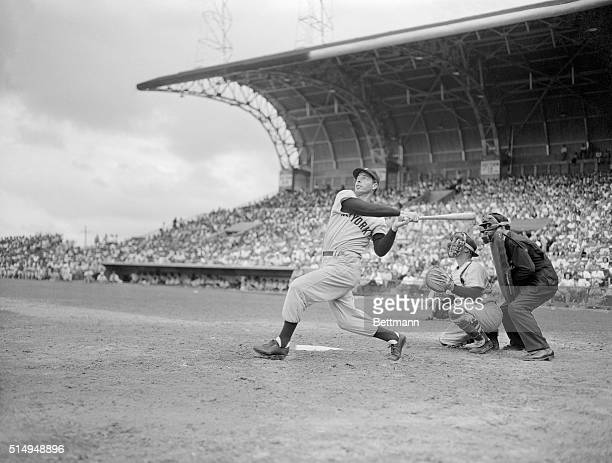 Joe DiMaggio of the Yankees slams one out of the park in the third inning of the World Champions' game with the Memphis Chicks The catcher is Don...