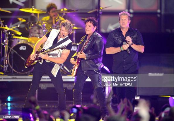 Joe Don Rooney and Jay DeMarcus of Rascal Flatts perform with Arnel Pineda of Journey onstage at the 2012 CMT Music awards at the Bridgestone Arena...