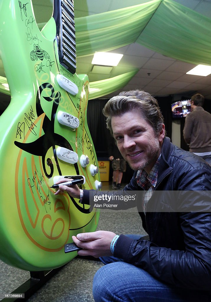 Joe Don Rooney of Rascal Flatts signs a giant Patron tequila guitar backstage at the CMA Awards to benefit the 'Keep the Music Playing' music education on November 3, 2013 in Nashville, Tennessee.