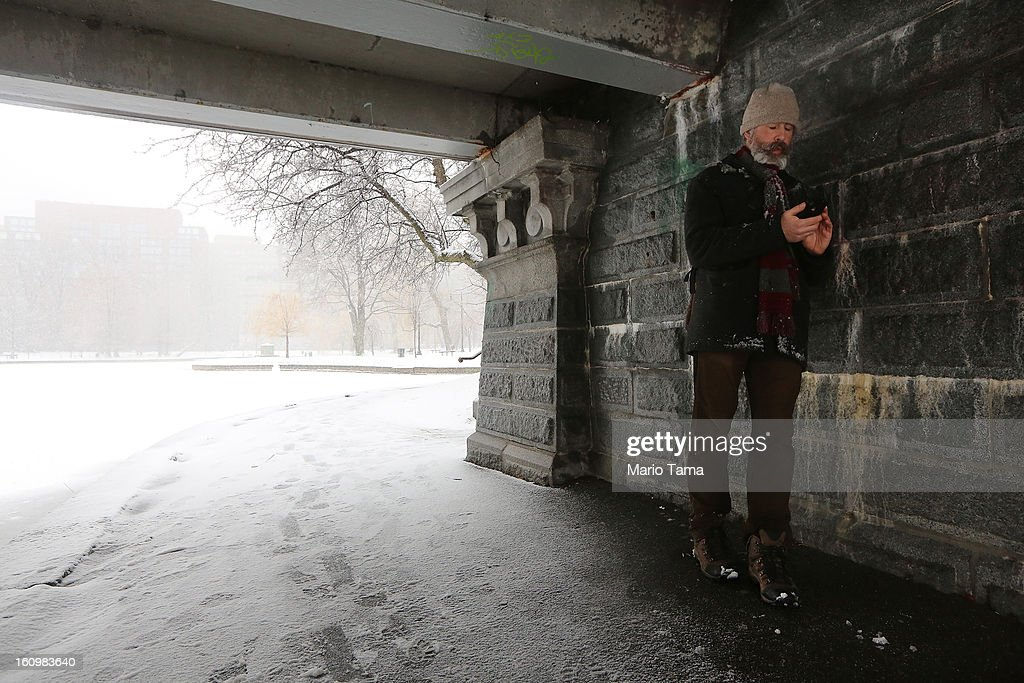 Joe Driscoll takes photos on his mobile device while taking shelter from the snow beneath a bridge in the Public Garden on February 8, 2013 in Boston, Massachusetts. Massachusetts and other states from New York to Maine are preparing for a major blizzard with possible record amounts of snowfall in some areas.