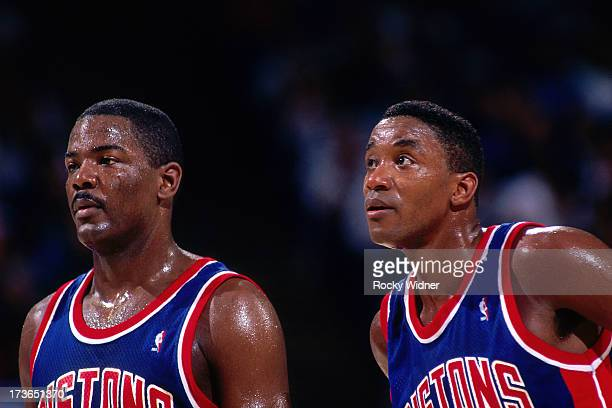Joe Dumars and Isiah Thomas of the Detroit Pistons look on against the Sacramento Kings during a game played on March 16 1993 at Arco Arena in...