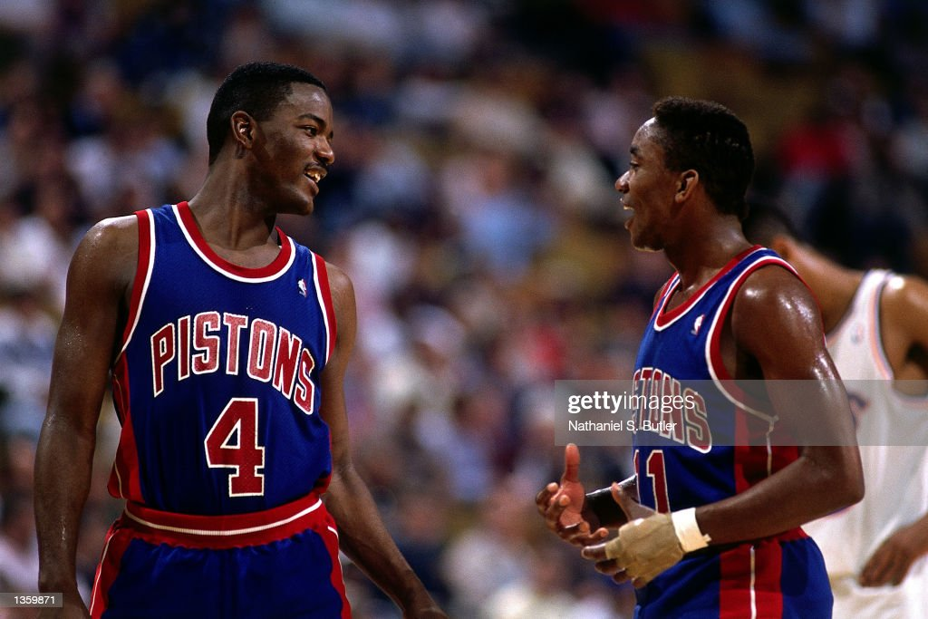 Joe Dumars and Isiah Thomas of the Detroit Pistons talk things over on the court in 1988 during the NBA game against the Cleveland Cavaliers in...