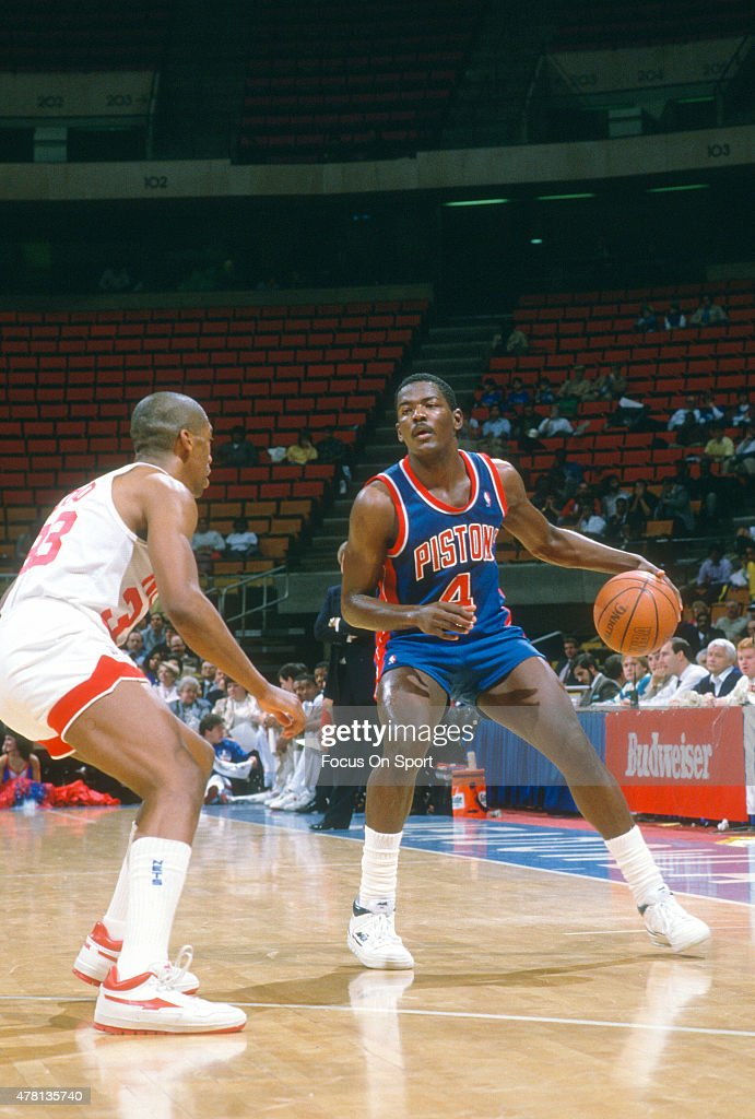 Joe Dumars of the Detroit Pistons dribbles the ball while defended by Leon Wood of the New Jersey Nets during an NBA basketball game circa 1986 at...