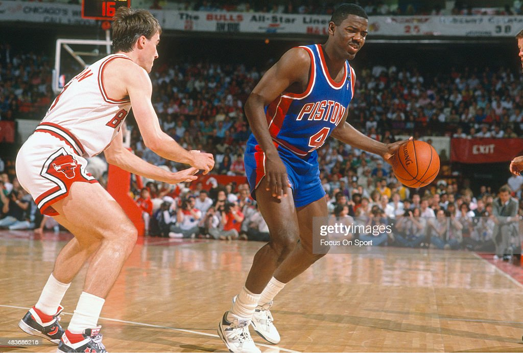 Joe Dumars of the Detroit Pistons dribbles the ball while guarded by John Paxson of the Chicago Bulls during an NBA basketball game circa 1987 at the...