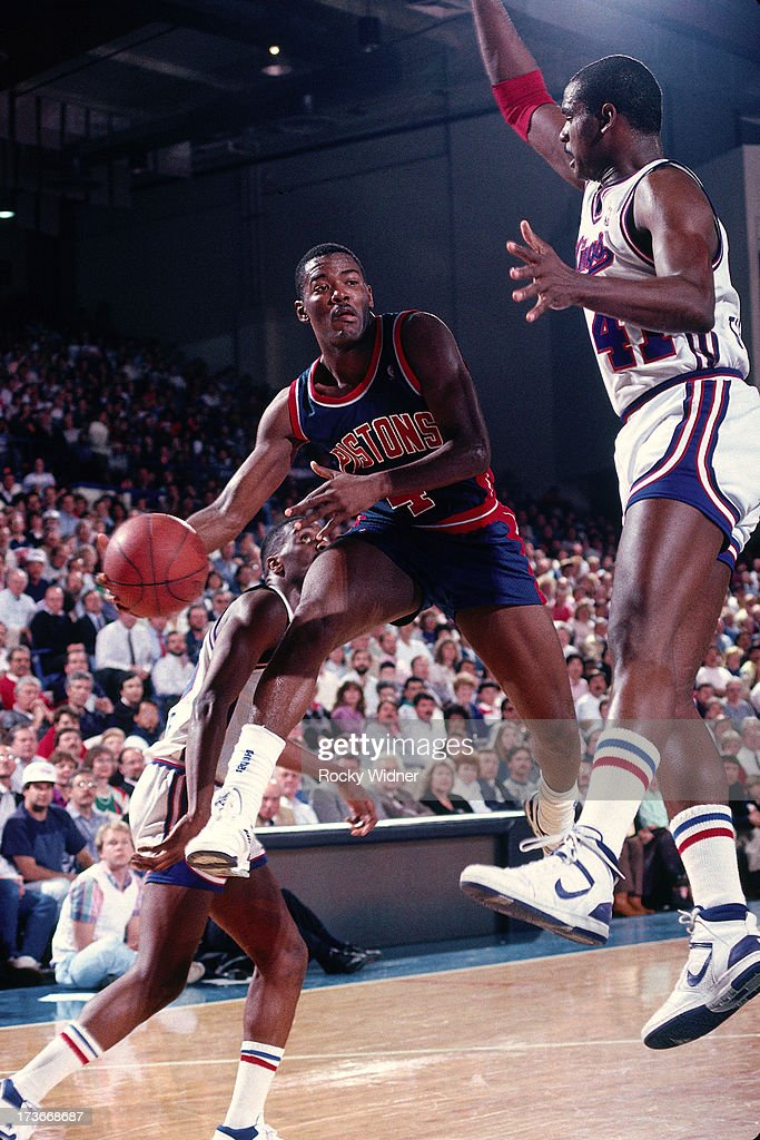 Joe Dumars of the Detroit Pistons passes the ball against LaSalle Thompson of the Sacramento Kings during a game played on February 23 1988 at Arco...