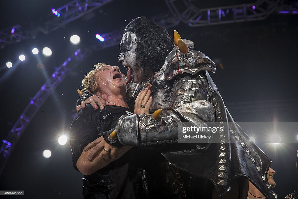 Joe Elliott of Def Leppard reacts as Gene Simmons leans in to lick his face after they performed the ALS Ice Bucket Challenge at Klipsch Music Center...