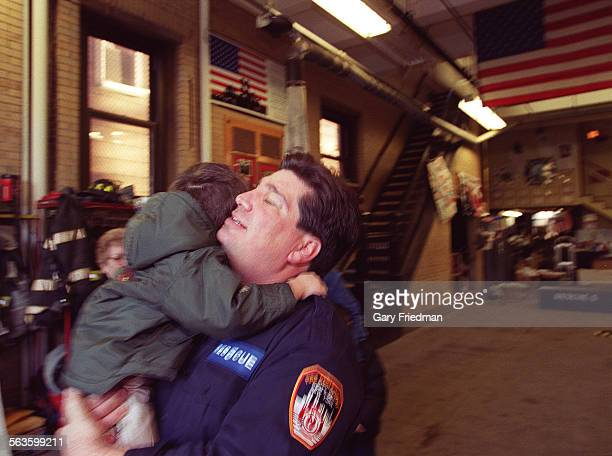 Joe Esposito hugs his son on Christmas Eve at Rescue 5 located on Staten Island NY